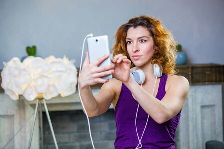 Portrait of an attractive woman with headphones on and holding smartphone in her hands choosing music Zdjęcie Seryjne
