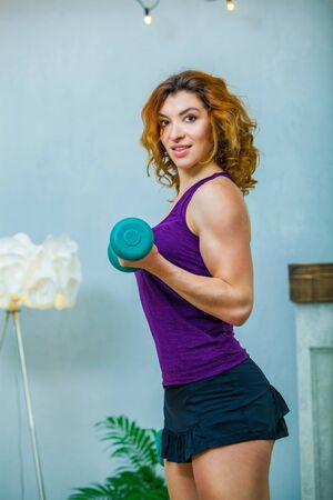 Sporty girl in purple top doing exercises on biceps lifting blue dumbbells at home Zdjęcie Seryjne