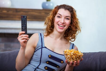 Beautiful girl holding TV remote control and a bowl of popcorn is laughing