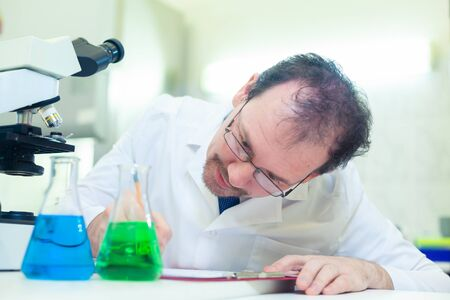 Chemist crazy. A mad scientist conducts experiments in a scientific laboratory. Intently records the results of the study.