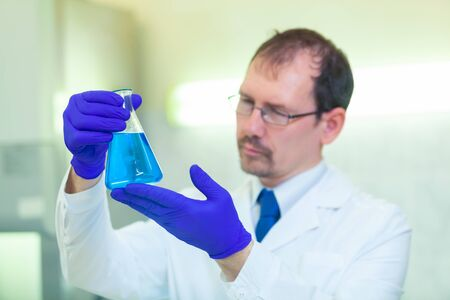 A scientist holds and studies a flask with blue liquid in a scientific laboratory