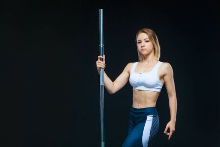 Close-up portrait of a fitness Muscular young girl posing with barbell at the gym isolated on a black background