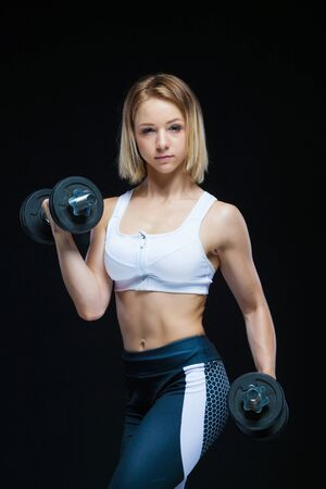 Close-up portrait of a fitness Muscular young girl posing with dumbbells at the gym isolated on a black background Reklamní fotografie