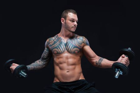 Tattooed strong muscular athletic man lifting up dumbbells on black background