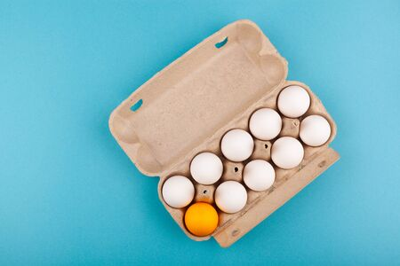 Egg Chicken eggs. Top view of an open gray box with white eggs Isolated on a blue background. One egg of a different color, an orange egg. The concept of focus, an outcast, not like everyone else, LGBT. Preparing for Easter. Banco de Imagens