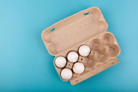Egg Chicken eggs. Top view of an open gray box with white eggs. Isolated on a blue background. The concept of a healthy lifestyle, getting pure protein. Proper Breakfast. Five eggs. Banco de Imagens