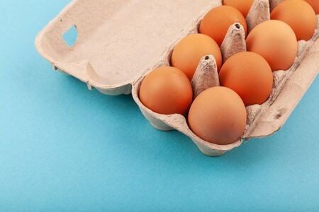 Egg Chicken eggs. Top view of an open gray box with brown eggs Isolated on a blue background. The concept of a healthy lifestyle, getting pure protein. Proper Breakfast. Dissati eggs. Banco de Imagens