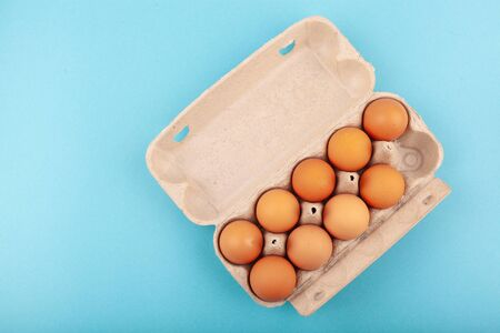 Egg Chicken eggs. Top view of an open gray box with brown eggs Isolated on a blue background. The concept of a healthy lifestyle, getting pure protein. Proper Breakfast. Nine eggs. Banco de Imagens