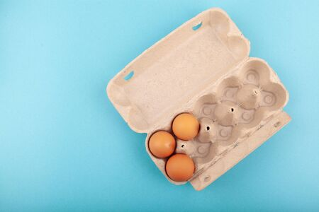 Egg Chicken eggs. Top view of an open gray box with brown eggs Isolated on a blue background. The concept of a healthy lifestyle, getting pure protein. Proper Breakfast. Three eggs.