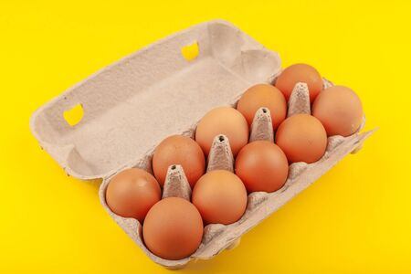 Egg Chicken eggs. Top view of an open gray box with brown eggs Isolated on a yellow background. The concept of a healthy lifestyle, getting pure protein. Proper Breakfast. .