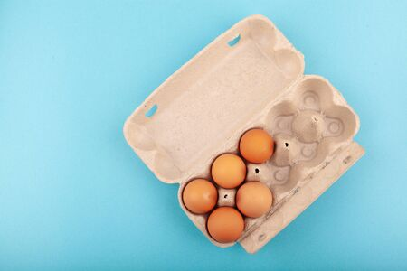 Egg Chicken eggs. Top view of an open gray box with brown eggs Isolated on a blue background. The concept of a healthy lifestyle, getting pure protein. Proper Breakfast. Five eggs. Banco de Imagens
