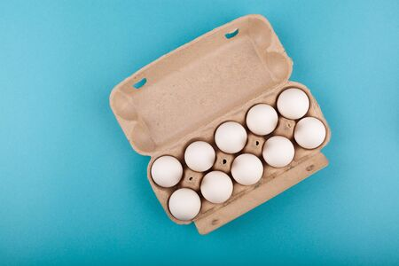 Egg Chicken eggs. Top view of an open gray box with white eggs. Isolated on a blue background. The concept of a healthy lifestyle, getting pure protein. Proper Breakfast