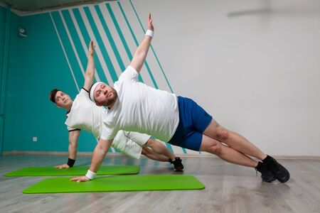 Fat man is working hard in the fitness gym with his personal trainer doing exercises on the mat at the limit of possibilities