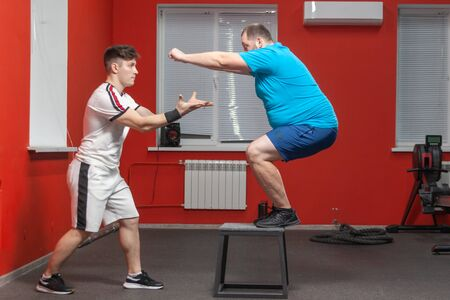 Eager overweight man is doing jumping in the gym under the guidance of a personal trainer Stock Photo