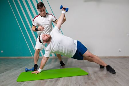 Fat man is working hard in the fitness gym with his personal trainer doing exercises with dumbbells at the limit of possibilities.
