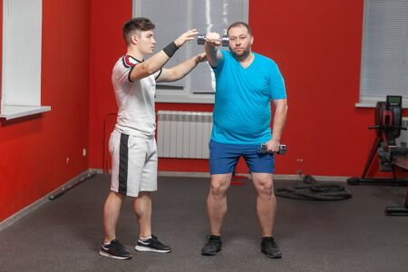 Personal fitness trainer shows to a fat man how to perform an exercise with dumbbells in a gym. Overweight
