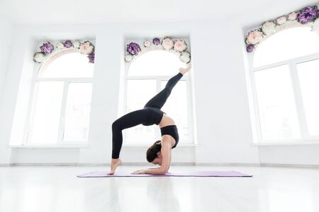 Young woman practicing yoga, standing in handstand exercise, working out, wearing black sportswear, on the floor near window