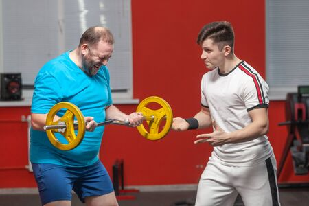 A fat man in the gym performs barbell lifting exercises at the limit of his powers under the guidance of a personal trainer. Overweight Stock Photo