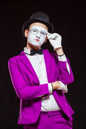 Portrait of male mime artist, isolated on black background. Young man in purple suit is touching his chin with a thoughtful look. Symbol of reflection, criticism