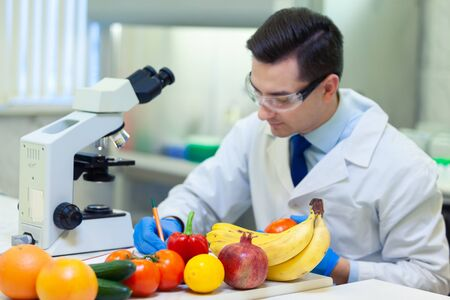 Laboratory worker examining fruits and vegetables and making analysis for pesticides and nitrates.