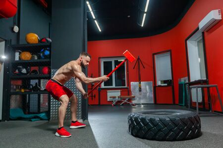 Full length portrait of strong muscular man performing sledgehammer workout in the modern gym Imagens
