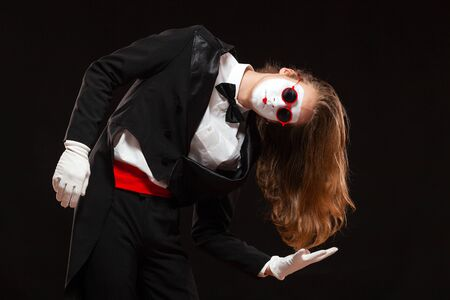 Portrait of male mime artist performing, isolated on black background. Man is standing leaning to the side showing the length of his hair