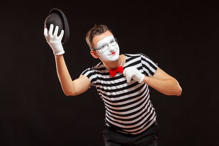 Portrait of male mime artist performing, isolated on black background. Man raises his hat and touches his bow tie. Symbol of greeting, introduction, friendship 版權商用圖片