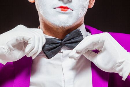 Portrait of male mime artist, isolated on black background. Close up of mans face. Man adjusts his bow tie.