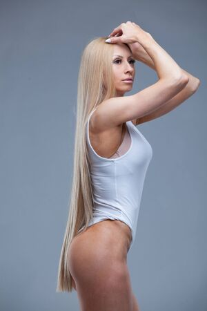 Side view portrait of young fitness woman in white gym leotard posing touching her hair isolated on grey background