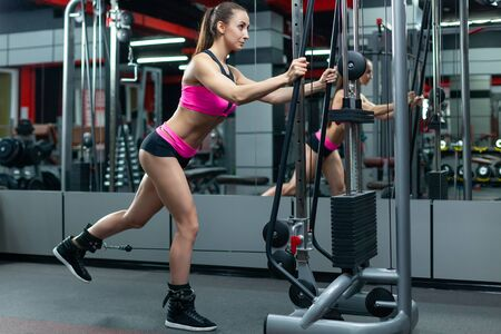 Nice muscular woman working in the gym pumping the posterior femoral muscle using special sports equipment