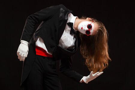 Portrait of male mime artist performing, isolated on black background. Man is standing leaning to the side showing the length of his hair.