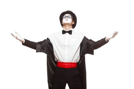 Portrait of a male mime artist performing, isolated on white background. Standing with his hands raised. Symbol of glory, fame, praise, arrogance, star