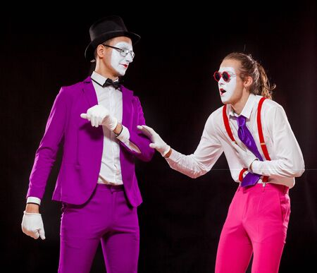 Portrait of two male mime artists, isolated on black background. A man in suspenders clutches his stomach and reach for a man in purple suit