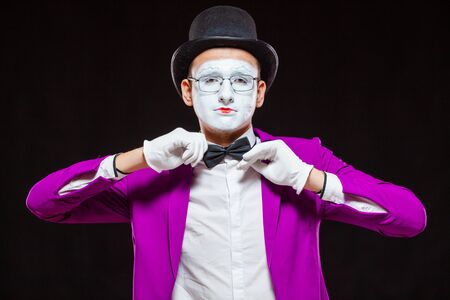 Portrait of male mime artist, isolated on black background. Close up of man face. Man adjusts his bow tie