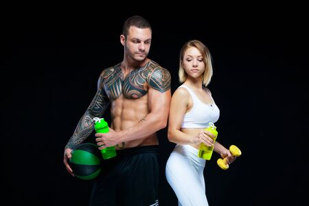 Fitness couple - woman and tattooed muscular man posing with water bottles and sport equipment over black background