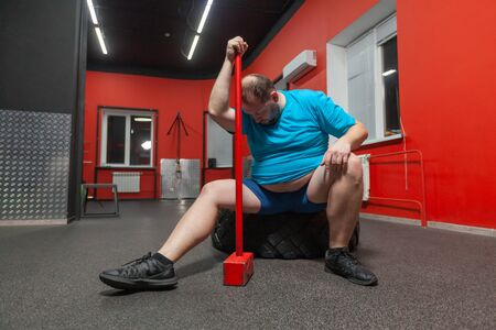 Potbellied man is sitting on a tire exhausted after performing sledgehammer and tire training in the gym. Excess weight