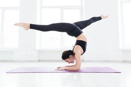 ヨガを練習する若い女性、ハンドスタンド運動に立ち、ワークアウト、黒いスポーツウェアを着て、窓の近くの床に