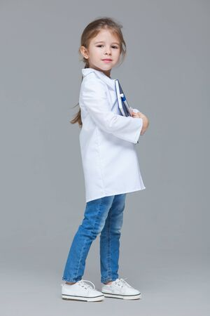 Adorable child girl uniformed as doctor is holding medical record isolated on grey background