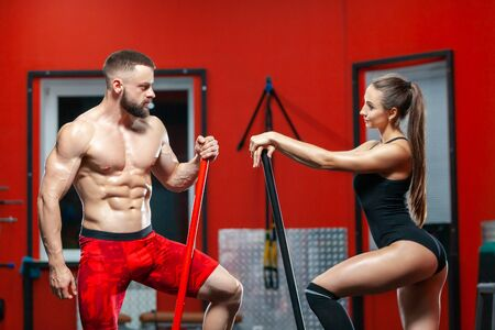 Portrait of muscular strong man and sexy fitness woman posing with sledgehammers and a tire in the gym