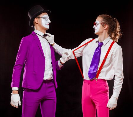 Portrait of male mime artists, isolated on black background. Two men wearing bright purple and pink suits adjust bow tie and suspenders to each other Banque d'images