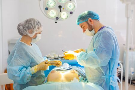 Hospital. Surgeon operates in the operating room. Completion of augmentation surgery.