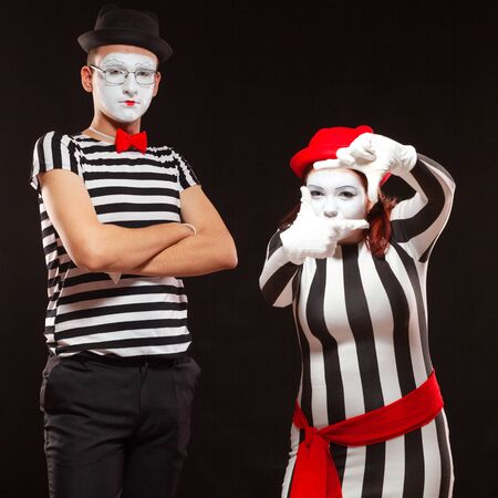 Portrait of two mime artists performing, isolated on black background. Man is standing with folded arms over his chest, woman folded her hands like holding a camera