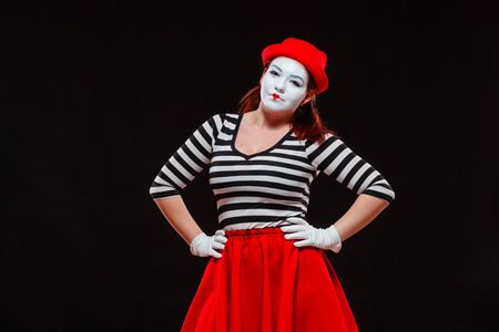 Portrait of female mime artist performing, isolated on black background. Woman in striped clothes and red skirt is standing with hands on her hips Stock Photo