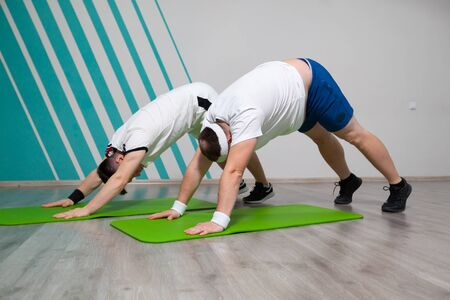 Fat man is working hard in the fitness gym with his personal trainer doing exercises on the mat at the limit of possibilities.