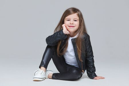 Baby girl with long hair in black leather jacket and leggings is sitting in the studio on grey background Foto de archivo