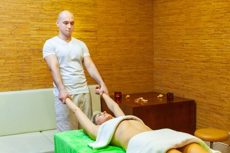 Photo of male massage therapist pulling woman arms doing traditional Thai massage on woman body in the spa salon 스톡 콘텐츠
