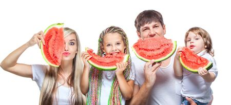 Portrait oh happy family with two kids holding watermelon slices in front of their faces isolated on white background 版權商用圖片