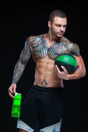 Muscular man bodybuilder with tattoos. Man posing on a black background with water bottle and ball