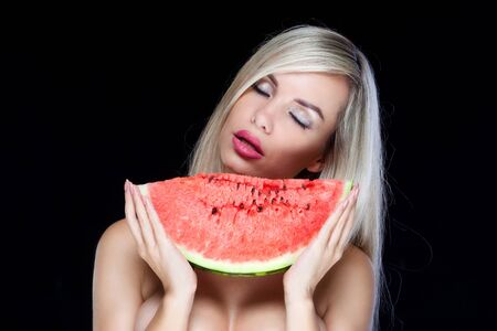 Sexy young blonde woman is posing with closed eyes wanting to bite a slice of watermelon isolated on black background Banque d'images