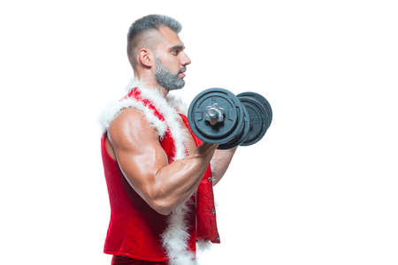 Sexy Santa Claus. Bodybuilder young handsome santa clause smile holds a dumbbells and shows off abs cubes at New Years eve and Christmas winter holiday white background. Stock Photo